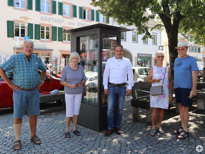 Henning Uhlich, Birgit Uhlich, Bürgermeister Dirk Harscher, Evi Schwörer, Max Schwörer vor dem Bücherschrank auf dem Marktplatz. Frau Uhlich und Frau Schwörer halten ein kleines Präsent in der Hand, was von der Stadt Schopfheim zum Dank ausgehändigt wurde